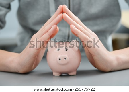 hands protecting and making roof over a piggy bank money box - stock photo