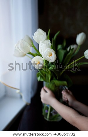 hands put a vase with a bouquet of tulips - stock photo