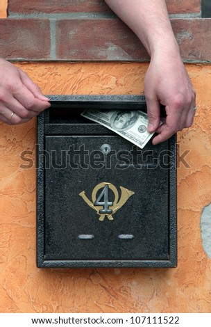 Hands puts money in the mailbox - stock photo