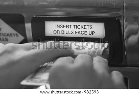 hands putting money into slot machine in Las Vegas - stock photo