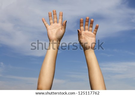 Hands raised against the sky. A pair of hands, lit by the sun, raised above somebody's head against a slightly cloudy blue sky. Hands belong to a 23 year old female. - stock photo