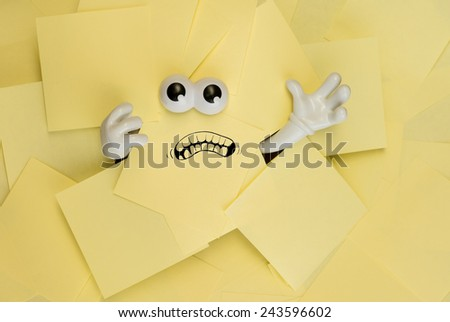 Hands reach out and eyes peer out from under several bright yellow sticky notes. A mouth is drawn onto one of the sticky notes as well. - stock photo