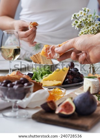 Hands reaching out for snacks at a party, selection of cheese, cured meat, fresh fruit, white wine and flowers - stock photo