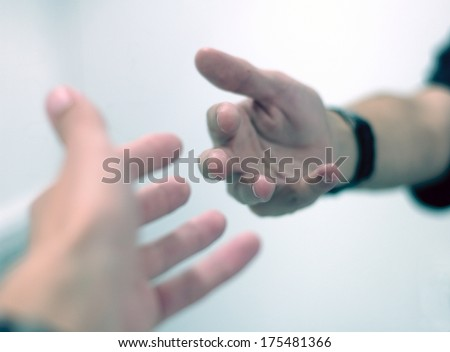 Hands reaching out to each other. - stock photo