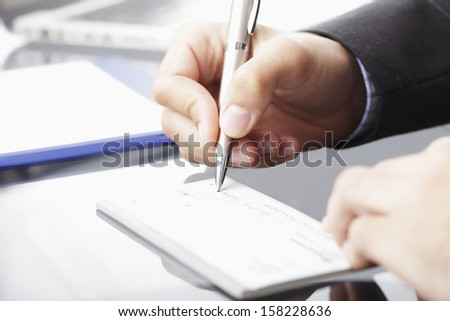 Hands ready to fill a cheque. - stock photo