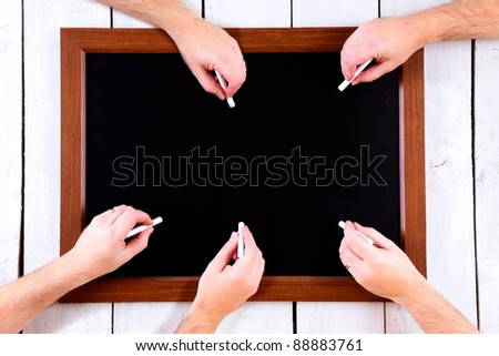 Hands ready to use chalk on a chalkboard - stock photo