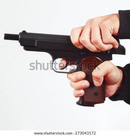 Hands reload semi-automatic gun on a white background - stock photo