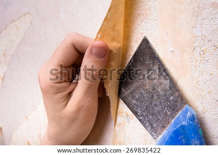 hands removing old wallpaper with spatula - stock photo