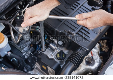 Hands repairing a car engine with a wrench - stock photo