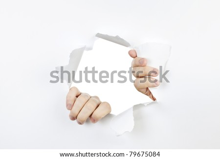 Hands ripping a hole in white paper with torn edges - stock photo
