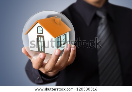 hands saving small house in glass ball - stock photo