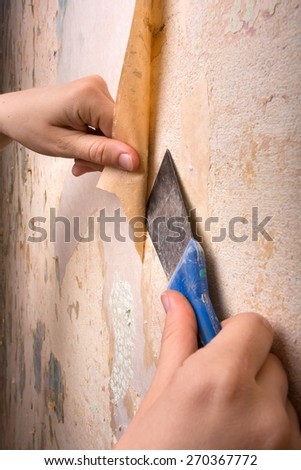 hands scraping off old wallpaper with spatula - stock photo