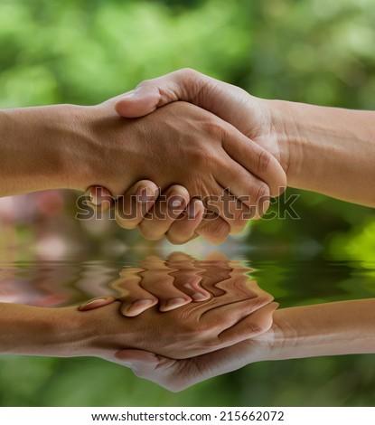 hands shake over nature background - stock photo