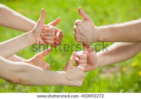 Hands showing  thumb up signs on natural green background - stock photo