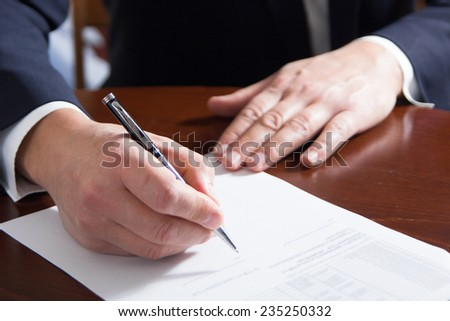 Hands signing business documents - stock photo