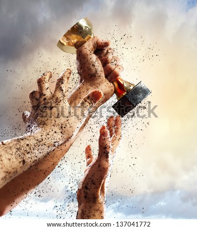 Hands squeeze the coup winner against lightning dark sky. - stock photo