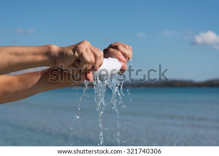 Hands squeeze wet towel against blue sky.