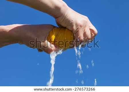 Hands squeeze wet yellow cloth against blue sky.