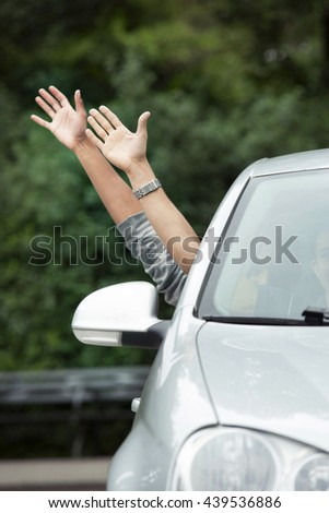 Hands sticking out of car - stock photo