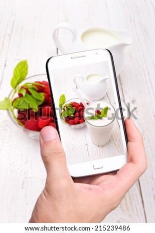 Hands taking photo milkshake with smartphone - stock photo