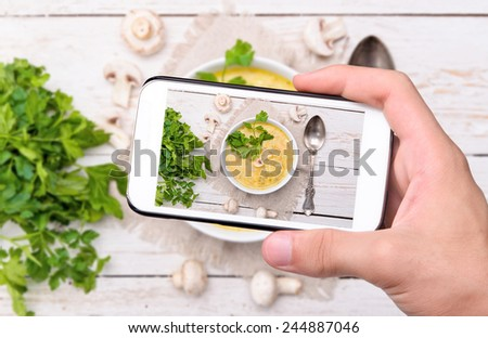 Hands taking photo mushroom soup with smartphone. - stock photo