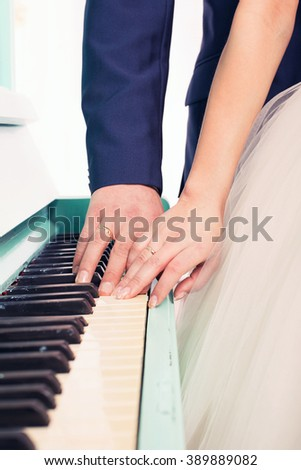 hands the newlywed on keys of Tiffany grand piano keys - stock photo