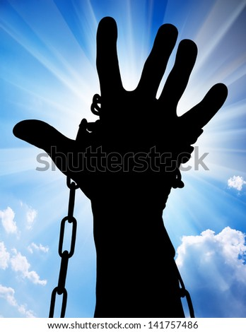 Hands tied up with chains against blue sky