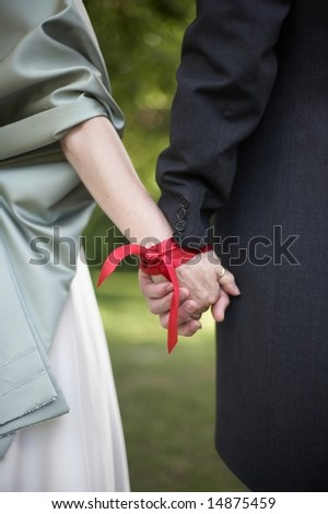 Hands tied with ribbon at traditonal handfasting wedding ceremony - stock photo