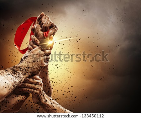 Hands tighten medal in a dark stormy sky. - stock photo