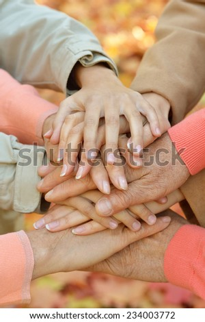 Hands together against the fallen leaves close-up