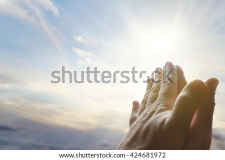 Hands together praying in bright sky - stock photo
