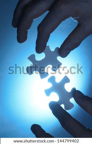 hands trying to fit two puzzle pieces together. - stock photo