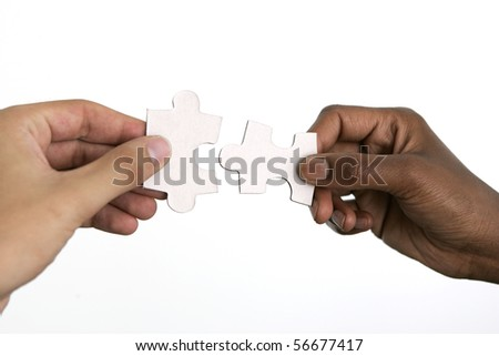 Hands trying to fit two puzzle pieces together, on white background - stock photo
