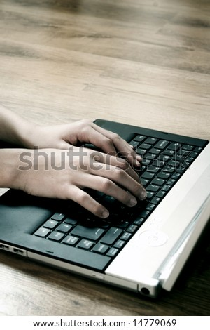 Hands typing on a laptop in home - stock photo