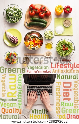 Hands typing on a laptop with fresh vegetables and healthy eating text concepts - stock photo