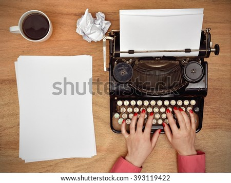 Hands typing on a Vintage typewriter. Blank paper on table - stock photo