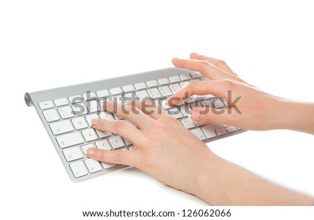 Hands typing on the remote wireless computer keyboard in an office at  workplace isolated on a white background - stock photo