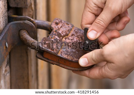 hands unlocking the padlock