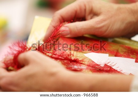 Hands Unwrapping Present - stock photo