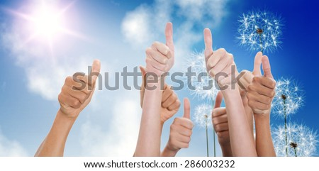 Hands up and thumbs raised against digitally generated dandelions against blue sky - stock photo