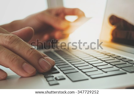 hands using laptop and holding credit card with digital business layers diagram as Online shopping concept - stock photo