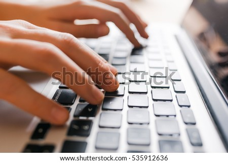 Hands using laptop type on keyboard, simple clean close up image with sun flare