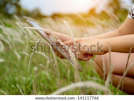 Hands using tablet computer in green field - stock photo