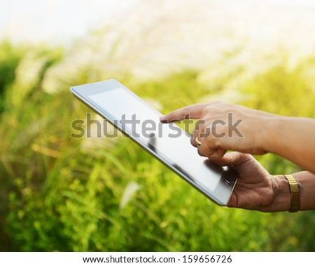 Hands using tablet computer in green field