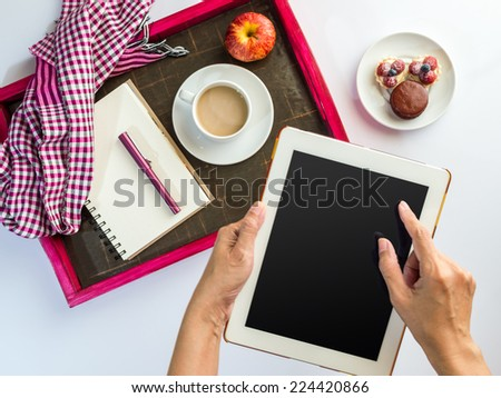 Hands using tablet computer with a wooden tray of light meal background - stock photo
