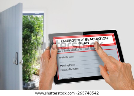 Hands using Tablet with Emergency Evacuation Plan beside Exit Door  - stock photo
