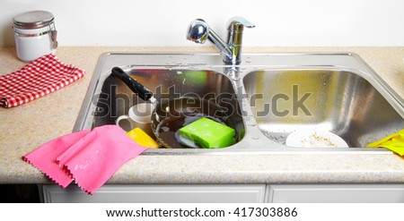 Hands washing dishes with running water from faucet in sink - stock photo