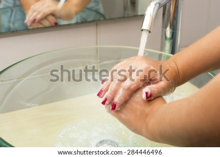 Hands washing with soap under running water, closeup