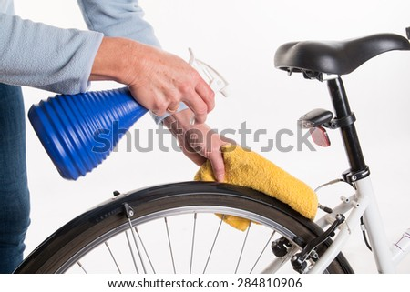 Hands with a cloth and water cleaning bicycle fender - spring cleaning