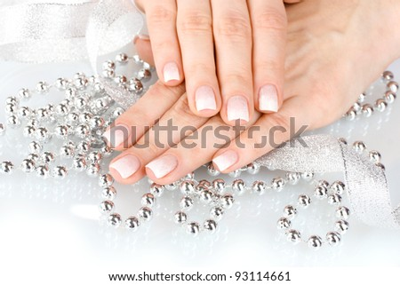 hands with beautiful winter design, ribbon and beads isolated on white - stock photo